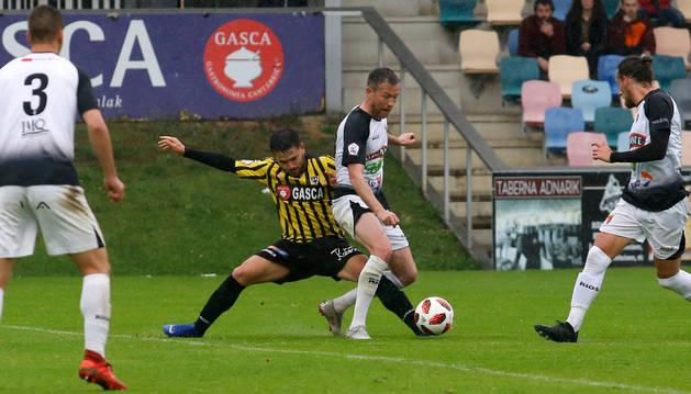 Foto de Víctor Bravo intenta defender el balón ante la entrada del rival del Barakaldo.