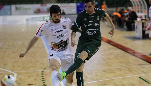 El pívot de Osasuna Magna, Adri Ortego, golpea el balón defendido por Iago Rodríguez, del Naturpellet Segovia.