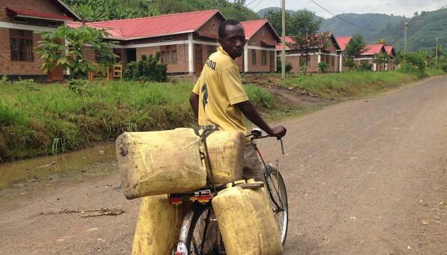 Un ruandés se desplaza en bicicleta en busca de agua con varias garrafas. El hospital de Nemba es un emblema de la cooperación navarra.