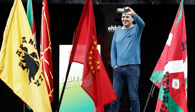 El líder de EH Bildu, Arnaldo Otegi, toma un vídeo desde el escenario en Pamplona.
