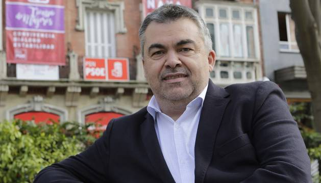 Santos Cerdán, sentado en un banco del Paseo de Sarasate. Tras él, el edificio donde está la sede del PSN, con sus carteles de campaña.