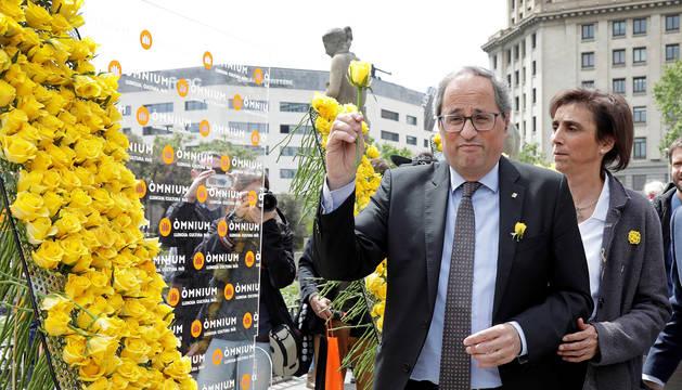 El presidente de la Generalitat, Quim Torra, coloca una rosa amarilla en el mural que recuerda a los independentistas presos instalado por Ómnium Cultural con motivo de la Diada de Sant Jordi.