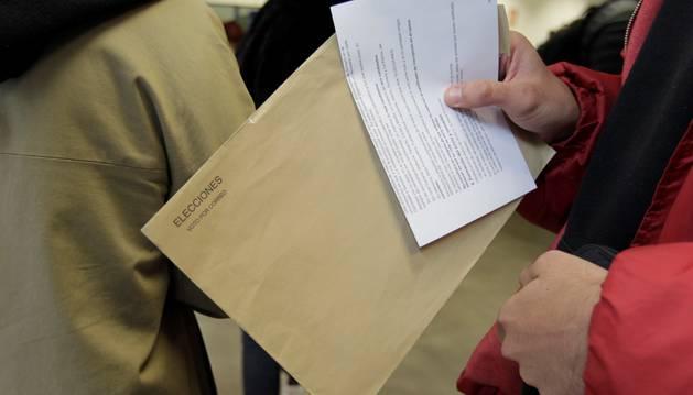 Foto de una persona porta un sobre del voto por correo para las elecciones del próximo 28A mientras espera su turno en una oficina de Correos de la capital.