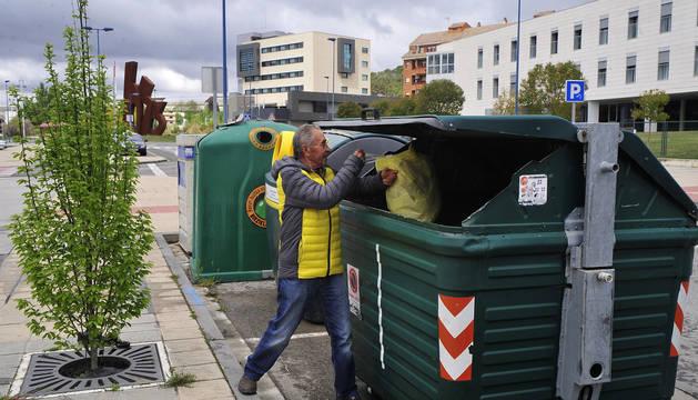 Una persona deposita una bolsa de basura en el contenedor en Tafalla.