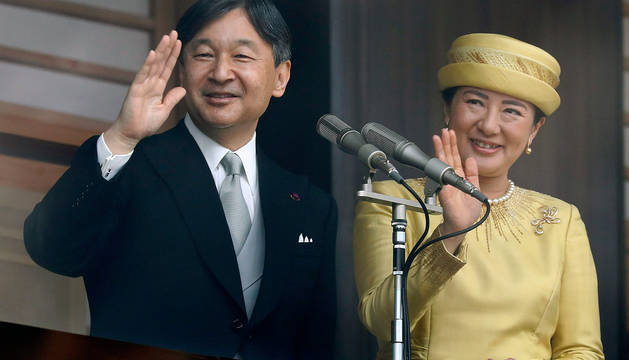 El emperador Naruhito y su esposa Masako saludan desde el Palacio Imperial de Tokio.