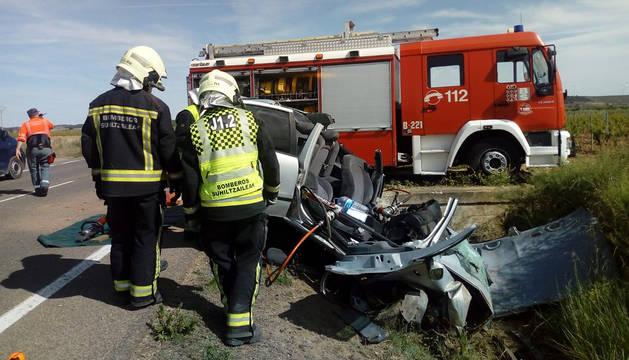 Dos efectivos de los Bomberos de Navarra junto al coche del que tuvieron que desatrapar al joven herido.