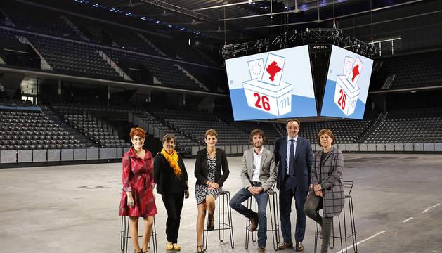 Desde la izquierda, Bakartxo Ruiz (Bildu), Marisa de Simón (I-E), María Chivite (PSN), Mikel Buil (Podemos), Javier Esparza (Navarra Suma) y Uxue Barkos (Geroa Bai), en el centro de la pista del Navarra Arena y con el logo electoral de Diario de Navarra  proyectado en las pantallas del marcador del pabellón.