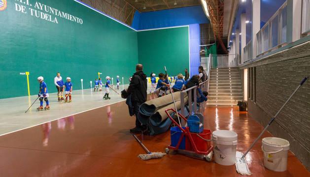 Imagen de varios cubos para limpiar las goteras en el frontón del polideportivo tras su remodelación.