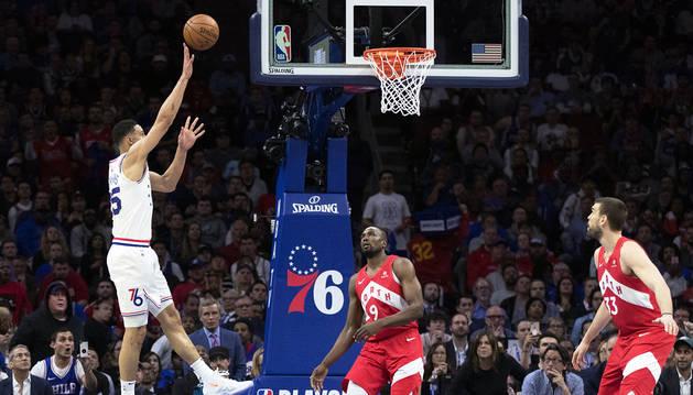 El jugador de los Sixers Ben Simmons lanza a canasta ante los rivales de