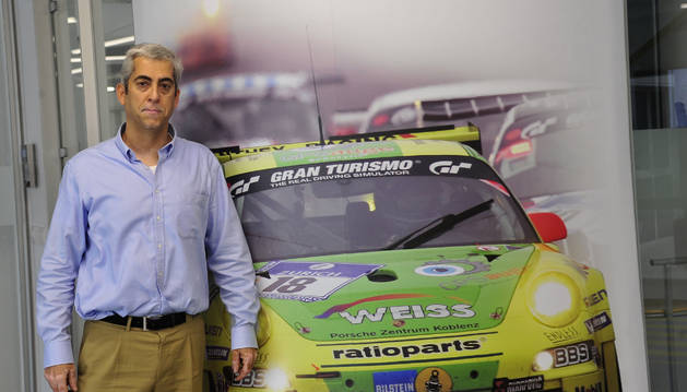 Foto de Guillermo Alonso, director de GKN Carcastillo, delante de una pared con la foto de un coche de carreras para quien fabrica  transmisiones.