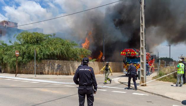 Agentes de policía y bomberos trabajan en las inmediaciones del incendio en Es Viver, Ibiza, horas después de que el siniestro fuera declarado.