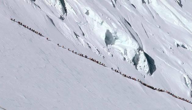 Una fila india casi continua de 'montañeros' aferrados a la cuerda fija, en las laderas del monte Everest.