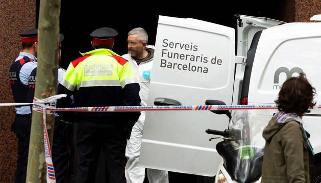 Mossos d'Esquadra y personal de los Servicios Funerarios retiran el cuerpo sin vida del hombre que ha fallecido tiroteado en la calle Comte d'Urgell, en el distrito del Eixample de Barcelona.