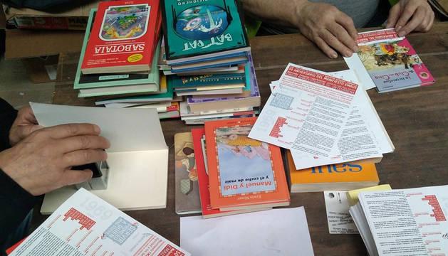 Varias personas preparan los libros que regalarán Traperos de Emaús.