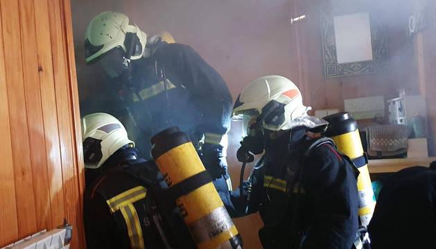 Los bomberos de Cordovilla intervienen en el interior de la vivienda, que tiene las paredes de madera.