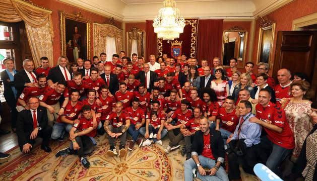Foto de familia de la plantilla rojilla con la corporación municipal en el Ayuntamiento de Pamplona.