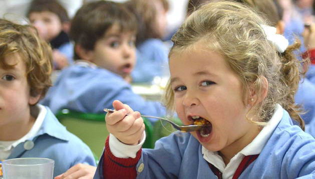 foto de Una niña, en un comedor escolar, se lleva la comida a la boca.