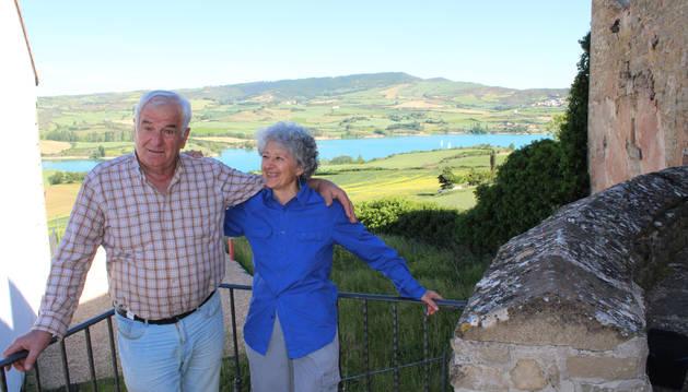 Miguel Ángel Nuin Ciriza y Begoña Cañada, esta semana, junto a la iglesia de San Esteban en Villanueva de Yerri, con el pantano de Alloz, al fondo. Visto desde allí el pueblo se eleva elegante en una pequeña meseta.