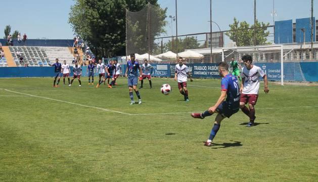 Un jugador del Móstoles centra un balón al área ante la presencia de Héctor Urdíroz, de la Peña Sport.