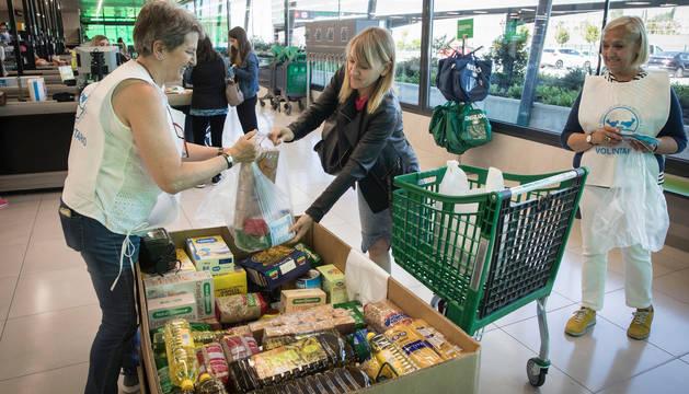 Una mujer entrega una bolsa llena de alimentos a una de las voluntarias, en un establecimiento de la comarca de Pamplona.