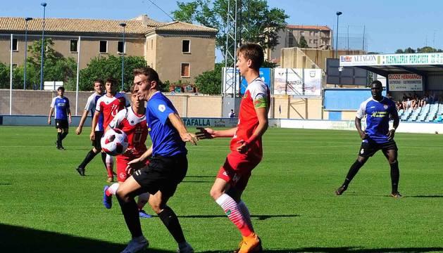 Fermín Úriz trata de controlar el balón ante la presencia de un jugador del Móstoles. Al fondo, Marcos Mendes sigue atento la jugada.