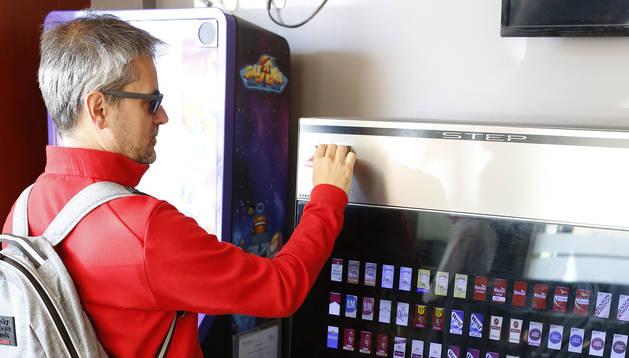 Una persona introduce un billete en una máquina expendedora de tabaco en un bar para sacar una cajetilla.