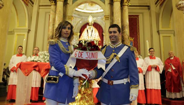 Foto de dos policías municipales, con el uniforme de gala, depositando un ramo de seis rosas ante la imagen de San Fermín.