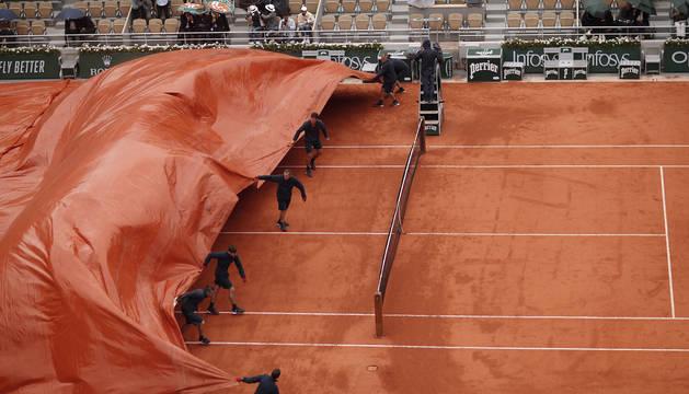 Varios operarios cubren con una lona la pista donde el tenista austriaco Dominic Thiem y el serbio Novak Djokovic, disputan una semifinal de Roland Garros, en París.