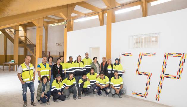 Foto de los participantes en el programa de Empleo Social Protegido, ante la nueva sede que han creado bajo las gradas de la plaza de toros de Tudela.