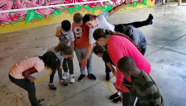 La artista de circo Sabiñe Ahechu, con camiseta blanca, rodeada de algunos de los menores que participan en las sesiones de circo social.