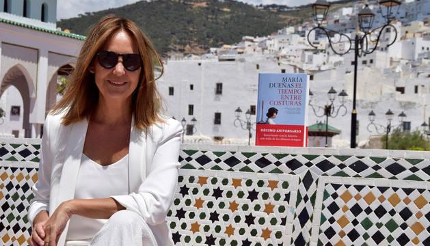 Foto de María Dueñas junto a su libro,durante su viaje a Tetuán.
