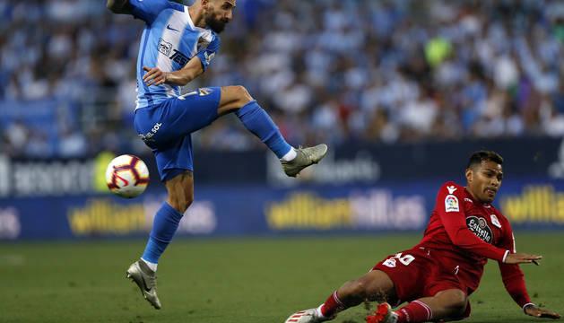 El defensa del Málaga Miguel Ángel Cifuentes chuta el balón ante el delantero argentino del Deportivo de La Coruña Matías Nahuel.