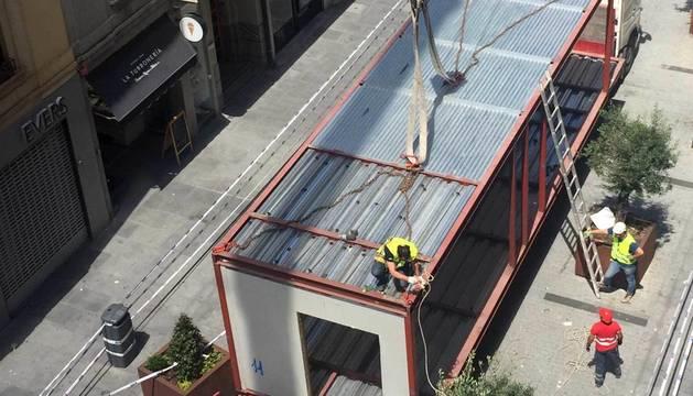 Varios operarios colocan los módulos del edificio en la calle Tafalla.
