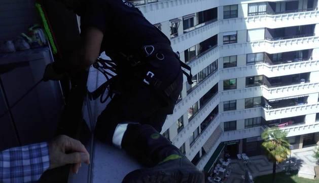 Un bombero, en la ventana de la mujer en la calle Abejeras.