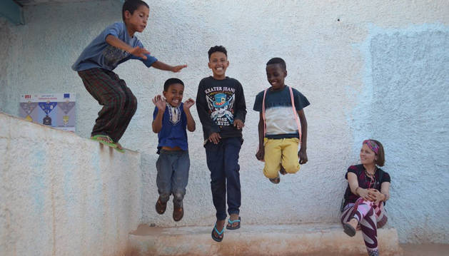 Foto de Yoana Irigaray, sentada, mira cómo juega Bamba, el niño más cercano a ella, y unos amigos durante su estancia en el Sáhara.