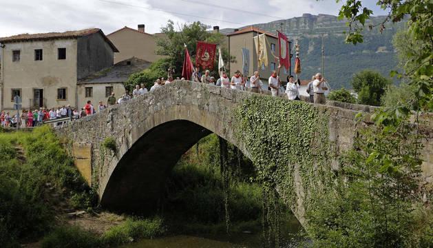 Foto del desfile con la Virgen del Rosario por el puente medieval que salva el río Arakil.