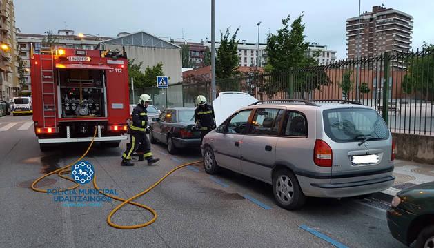 Foto de los bomberos, mientras sofocan el fuego generado en un coche al arrancarlo, en la calle Pintor Maeztu.
