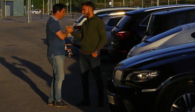 Braulio Vázquez choca la mano con Roberto Torres en los aledaños del estadio de El Sadar.
