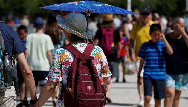 Una mujer, protegiéndose del sol con un paraguas.