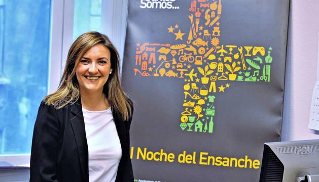 María Jesús Alonso Arteaga, en las nuevas oficinas de Ensanche Área Comercial, en el Paseo de Sarasate, junto al cartel que anunció la primera edición de Ensanche La Nuit.