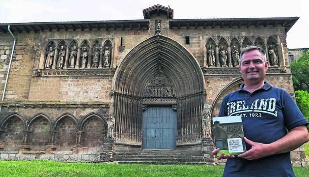 Andrés Valencia Ciordia, con el libro del que es autor en la explanada que se extiende junto a la iglesia del Santo Sepulcro de Estella.