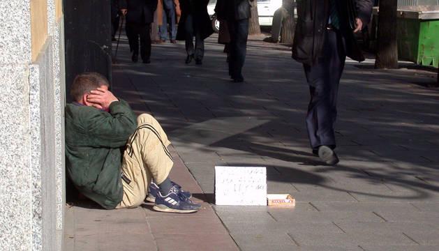 Una persona pide dinero en la calle.