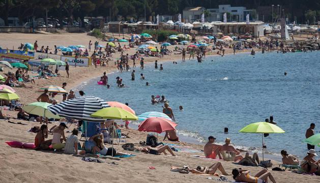 Varios bañistas se refrescan en la playa de Sant Feliu de Guixols.
