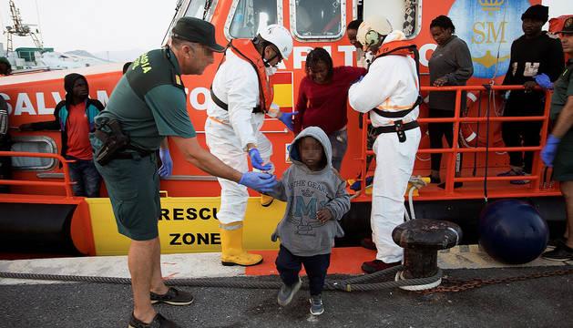 Un agente de la Guardia Civil ayuda a desembarcar a un niño que fue rescatado por Salvamento Marítimo en el mar de Alborán.