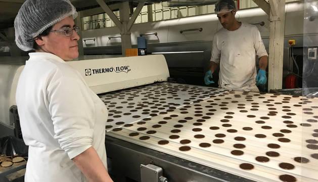 Trabajadores de la línea 1 de Digestive Finas, en la bañadora de chocolate a la que llega la galleta una vez enfriada.