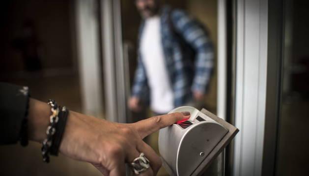 Una mujer registra con su huella dactilar su entrada al centro de trabajo.