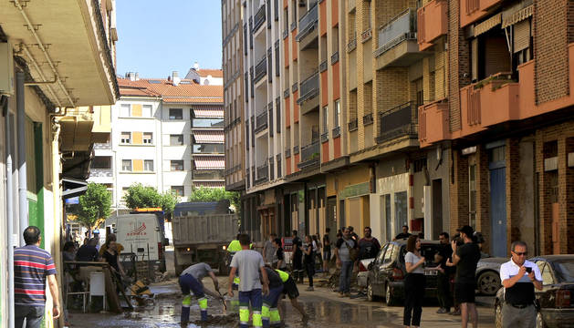 Foto de trabajos de desciegue y limpieza, ayer, en la calle Martínez de Espronceda, una de las más afectadas por las inundaciones del pasado lunes. Los coches volvían a estar aparcados en la zona.