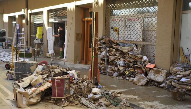 Basura, escombros, género dañado y persianas de negocios bajadas en la Calle Martínez de Espronceda, balance de las riadas del lunes en Tafalla.