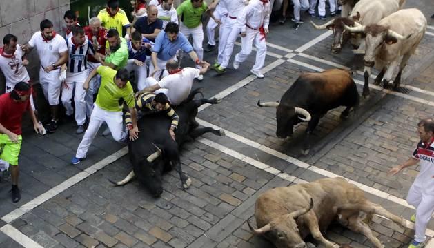 Momentos de tensión cuando el morlaco jabonero de la ganadería de Núñez del Cuvillo perdió pie en la calle Estafeta y cayó al suelo, rodeado de mozos.