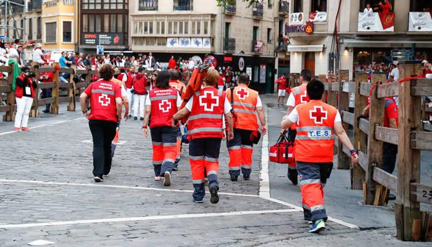 Foto de voluntarios de Cruz Roja de espaldas, caminan en sentido contrario de la carrera.